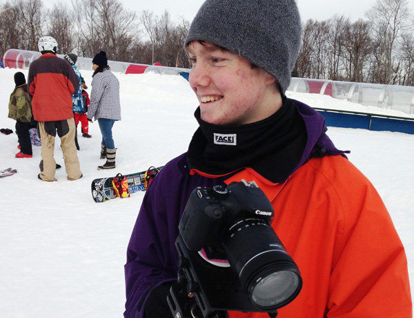 A young filmmaker smiling on a snowy ski hill