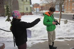 Two students working with a camera in the snow