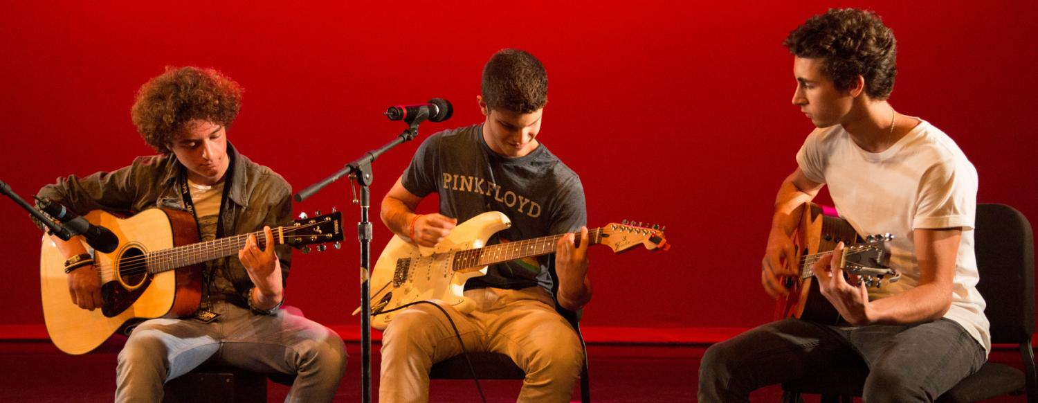Guitarists play their guitars during Summer Music Camp