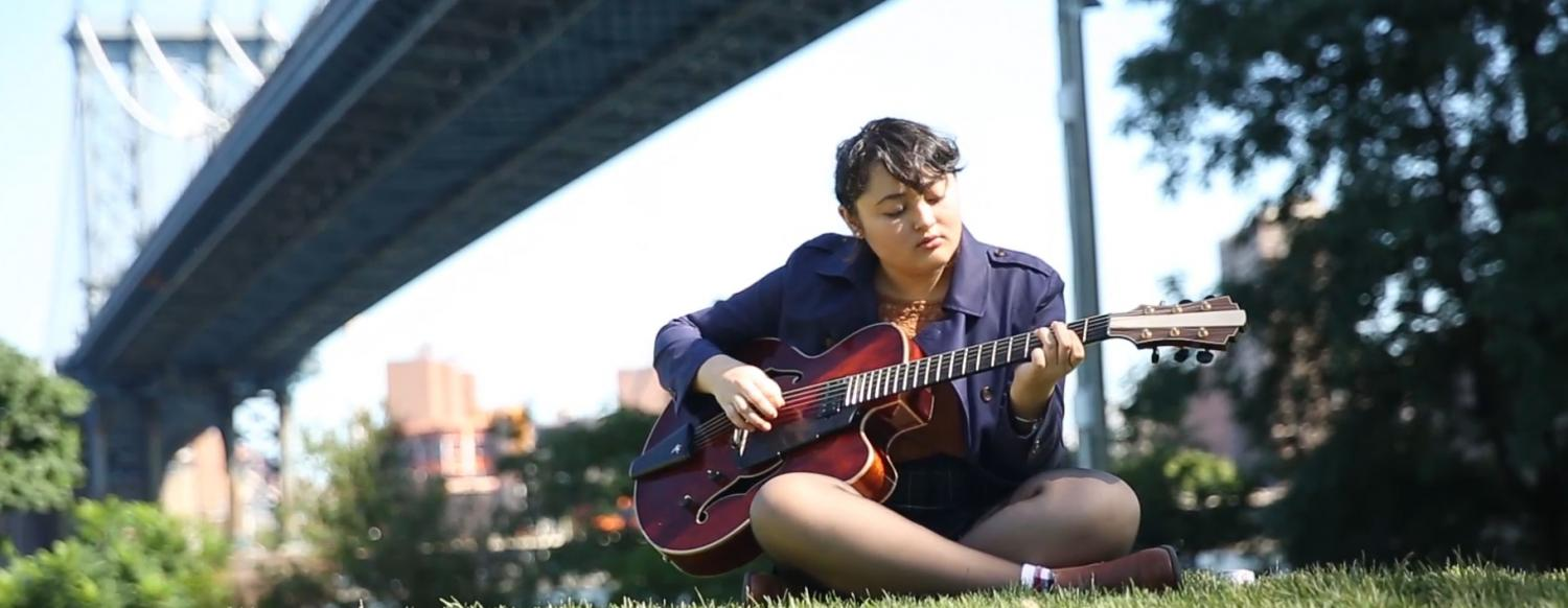 Teen musician plays guitar in New York City Summer camp
